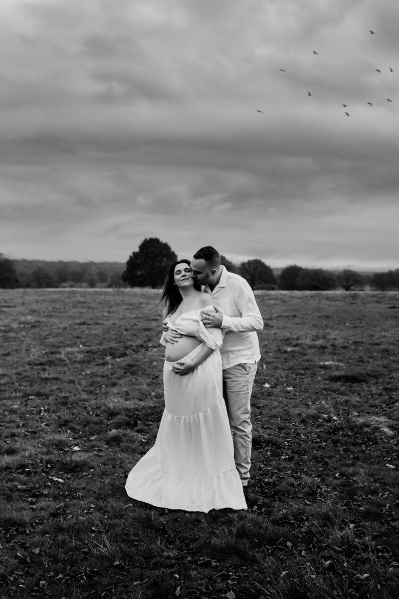 London Family Photographer, a man kisses his partner, she is smiling and holds her pregnant belly at the park