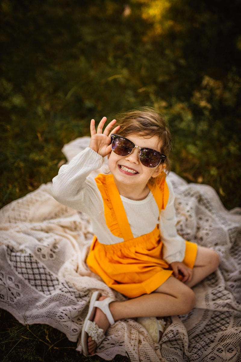 London Family Photographer, a young girl smiles as she holds onto a large pair of sunglasses on her face, she sits on a blanket