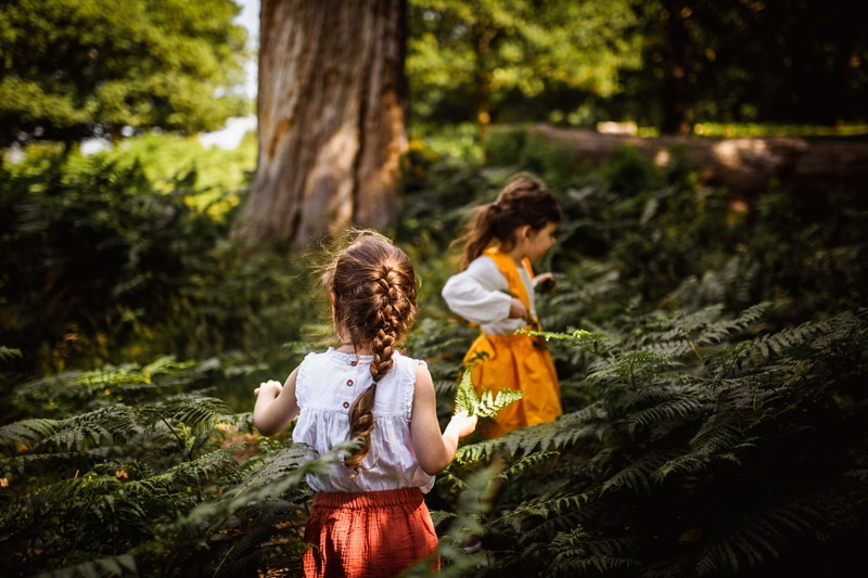 London Family Photographer, two young girls navigate through ferns in the forest, they are happy exploring