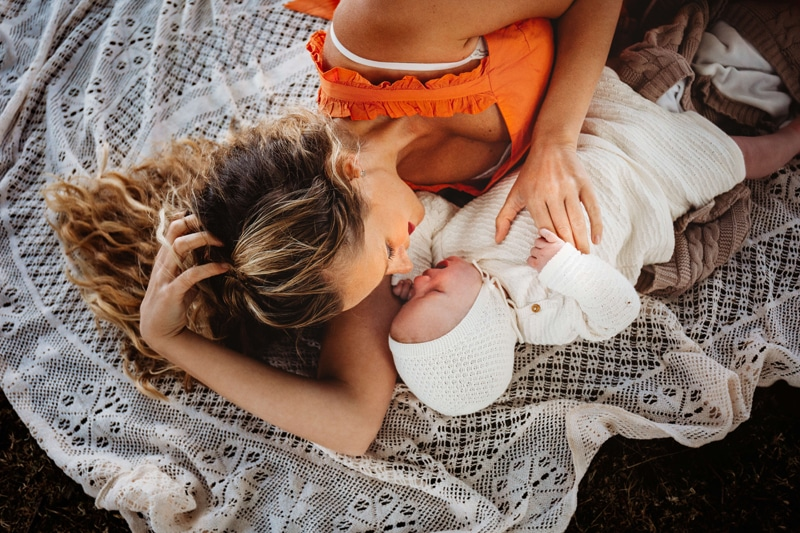 London Family Photographer, mother lays on a blanket outdoors doting on baby