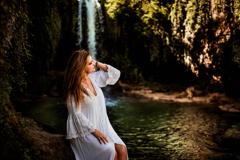 London Family Photographer, a woman in a white dress sits relaxing near a lush green waterfall setting