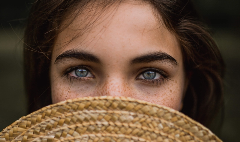 London Family Photographer, a young woman pokes her blue eyes out from behind a straw hat hiding her face