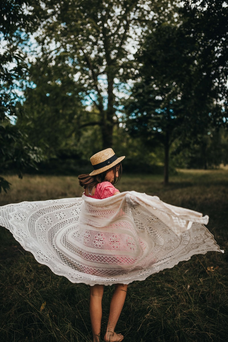 London Family Photographer, a young girl twirls her blanket through the air in the outdoors