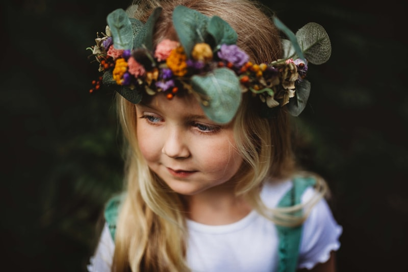 London Family Photographer, a young toddler girl stands outside with flower crown adorning her head