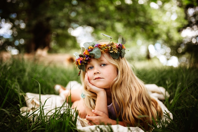 London Family Photographer, a young girl lays on a blanket in the grass with a floral crown in her hair