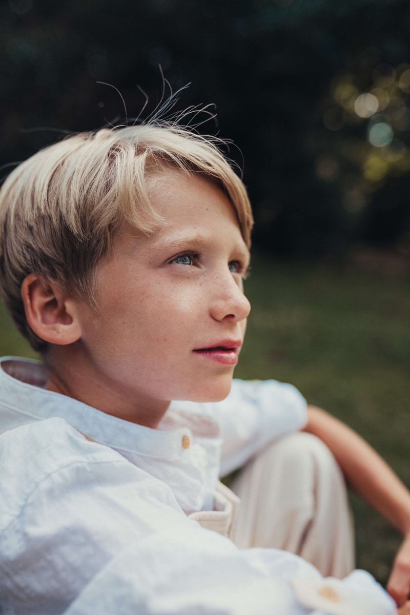 London Family Photographer, middle age boy sits pondering outdoors
