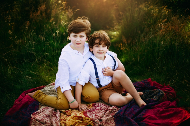London Family Photographer, two brothers sit close on a blanket in a lush grassy area