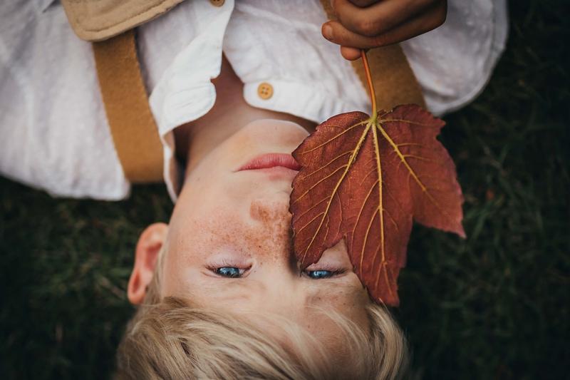 London Family Photographer, a boy lays in the grass with a large dry leaf covering part of his freckled face