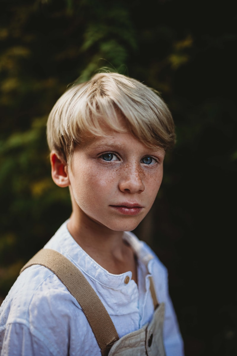 London Family Photographer, a little boy stands outdoors, freckles cover his face and he wears overalls