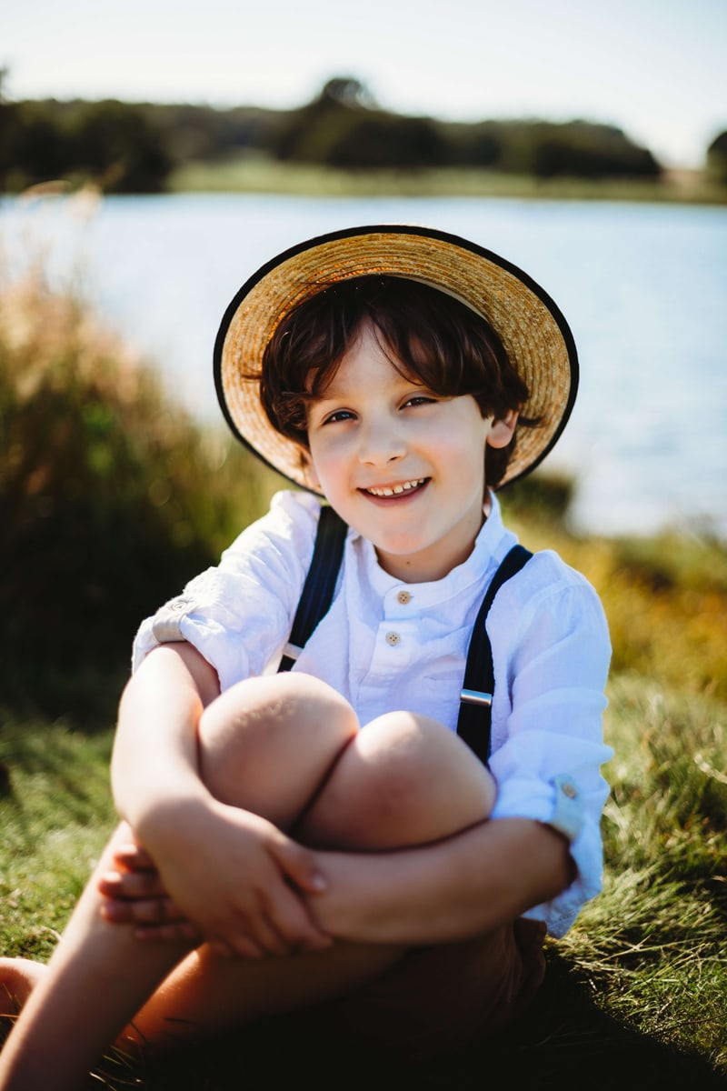 London Family Photographer, a young boy sits in the grass with a straw hat near a lake