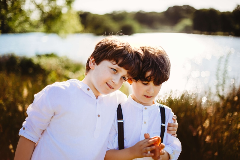 London Family Photographer, an older brother has his arm around his younger brother at the lake