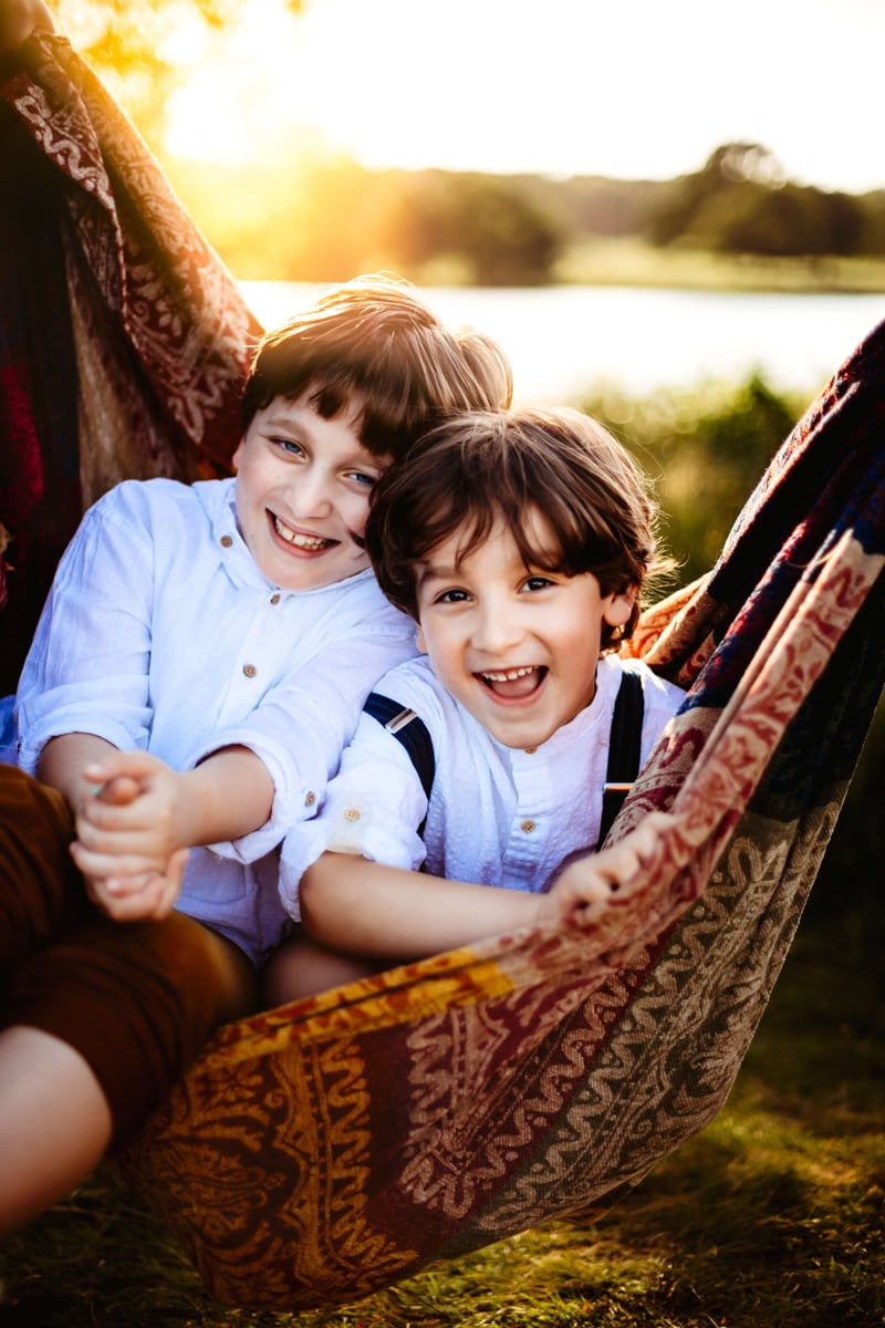 London Family Photographer, two brothers share a hammock outdoors, both giggling
