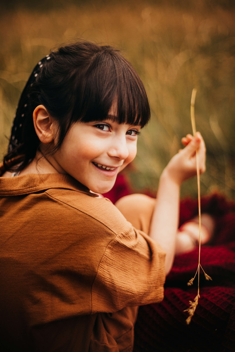 London Family Photographer, a young smiling girl holds up a piece of straw she has plucked