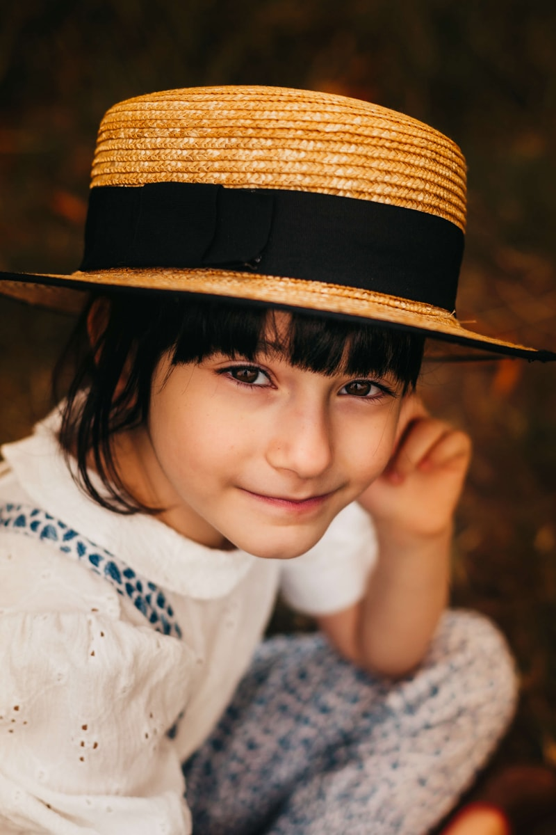 London Family Photographer, a young child sits pondering, smiling, and wearing a straw hat