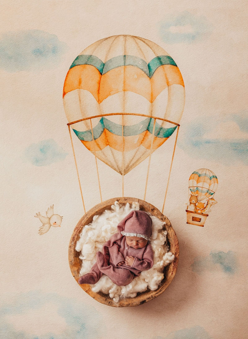 London Family Photographer, a baby lays sleeping a round basket, the floor beneath is painted with a hot air balloon, as if baby was floating away
