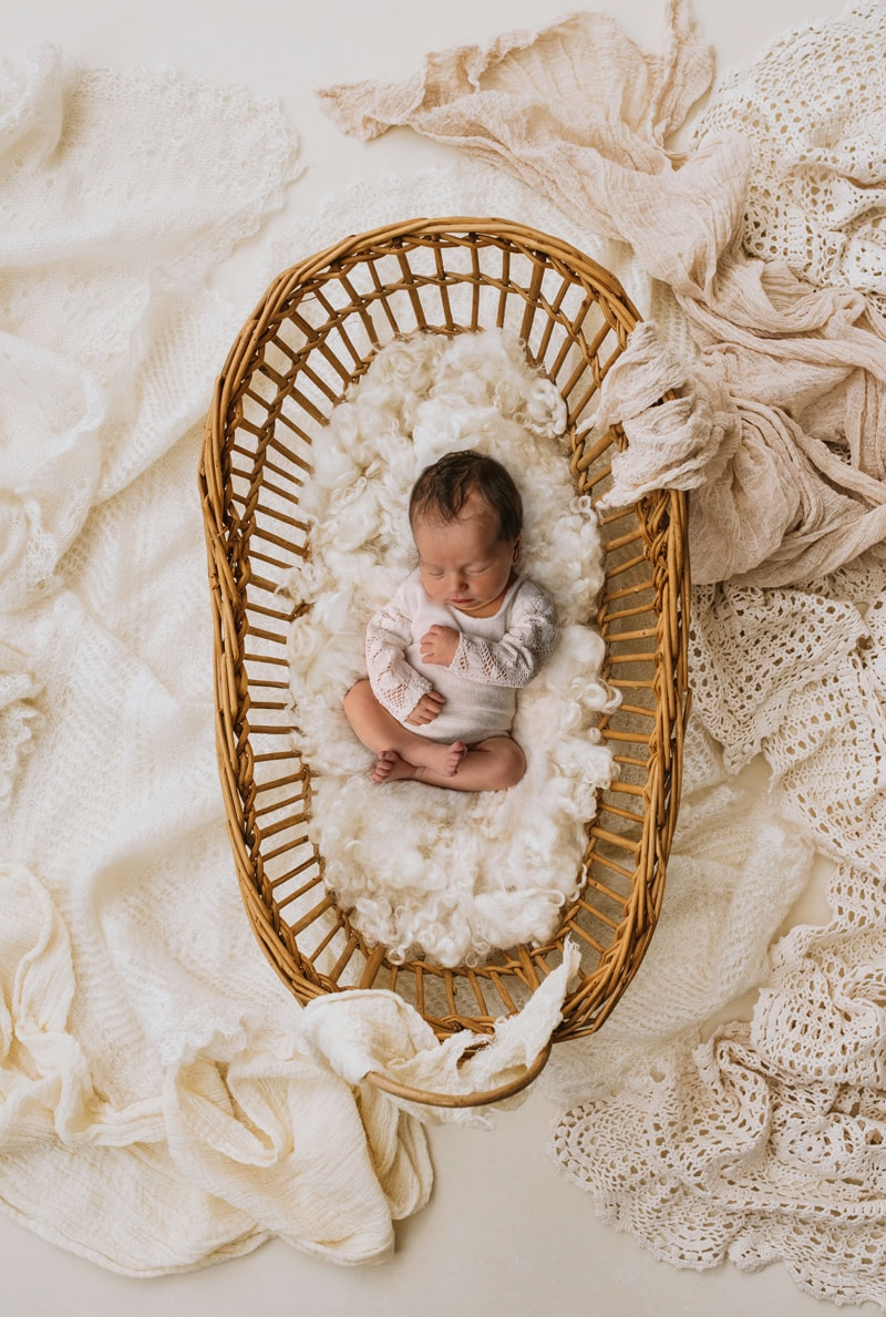 London Family Photographer, little newborn baby cozy in a basket with white linens