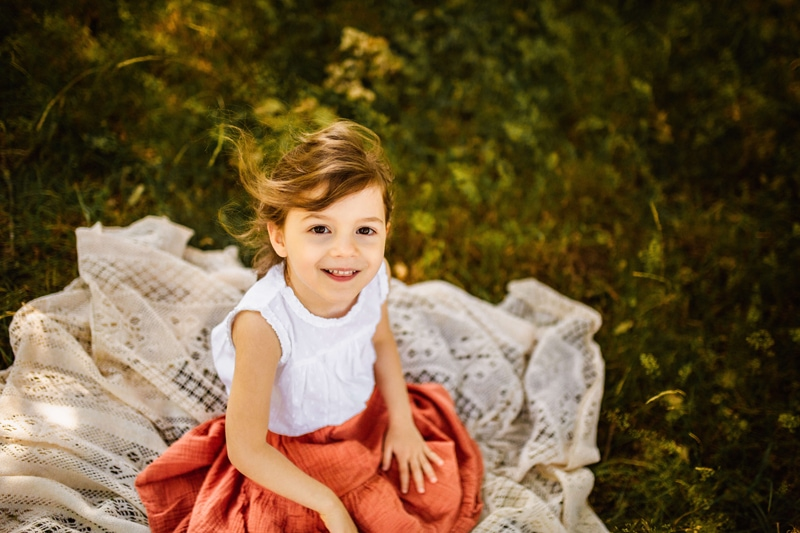 London Family Photographer, a young girl sits on a blanket outdoors in the grass, she is smiling