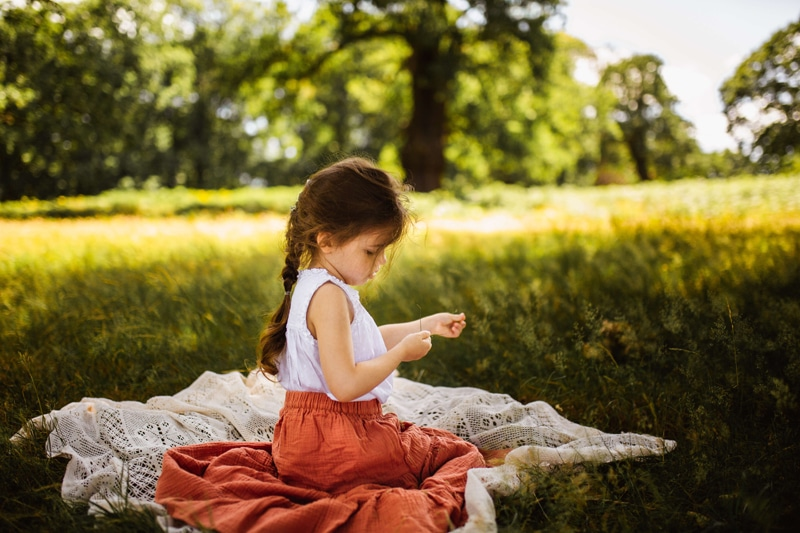 London Family Photographer, a girl sits on a blanket in a field focused on a blade of grass