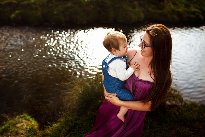 London Family Photographer, woman holds onto her baby smiling, her baby smiles back, they are by the lake