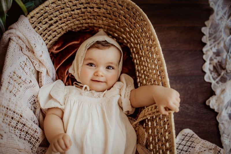 London Family Photographer, a baby lays smiling in a basket, her hand grips the wicker edge