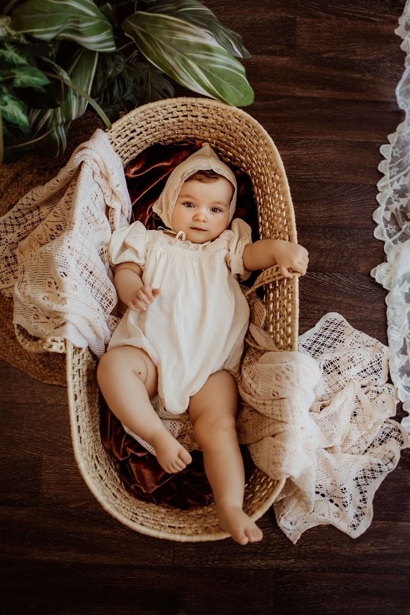 London Family Photographer, Baby lays in a basket ready to be bundled