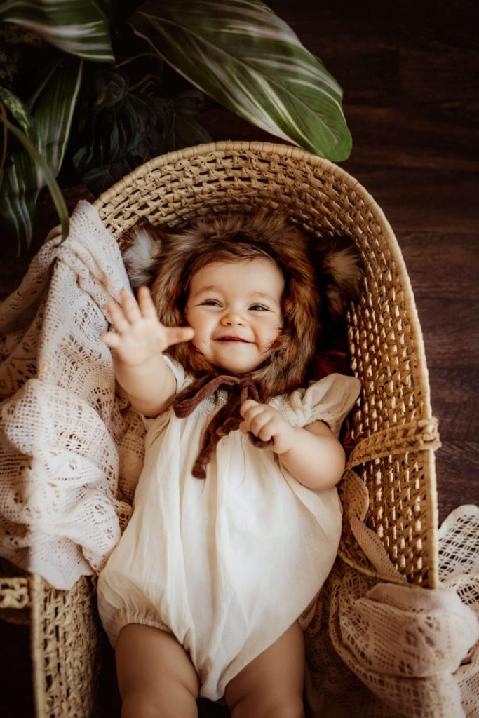 London Family Photographer, baby in Moses basket reaching their hand toward the camera