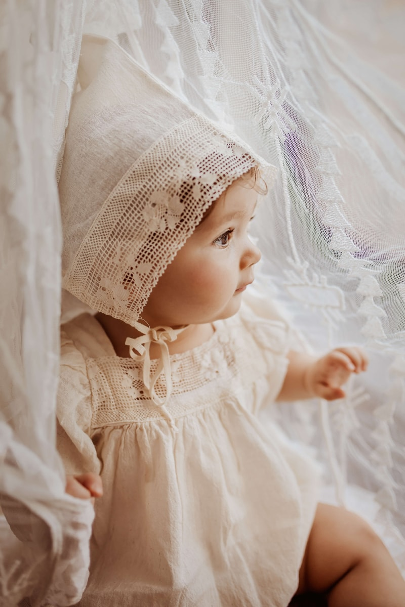 London Family Photographer, a happy baby girl lays in white linens
