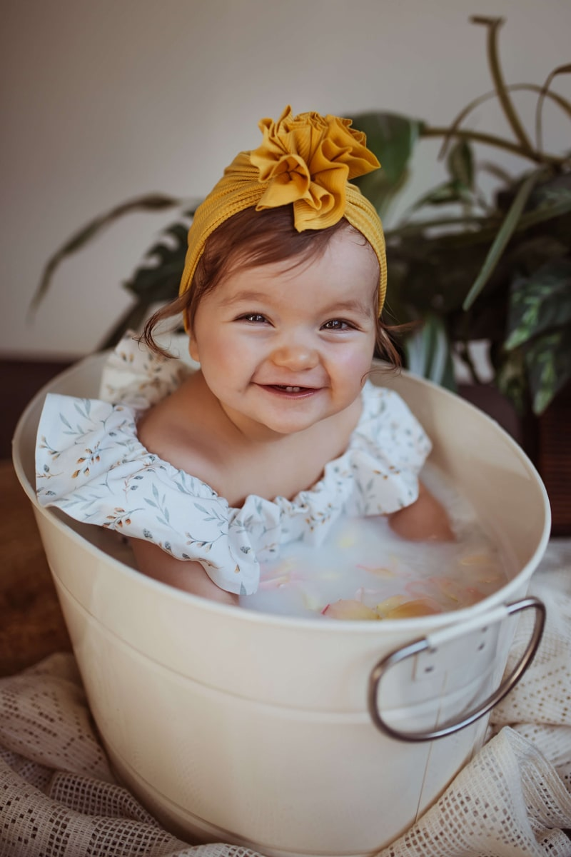 London Family Photographer, a young girl sits soaking in a milk bath happy