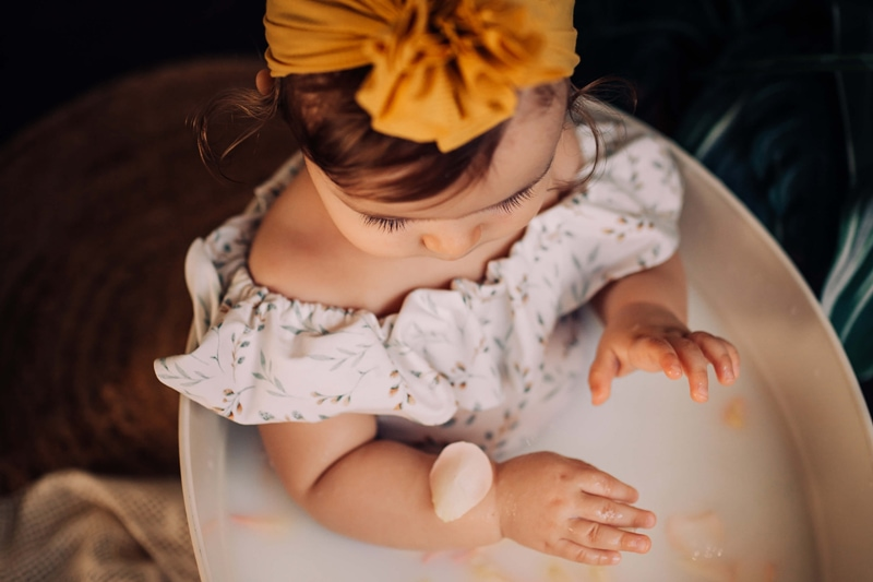 London Family Photographer, a young girl dressed in flowery attire and a large bow, sits in a milk bath with flower pedals on her hands