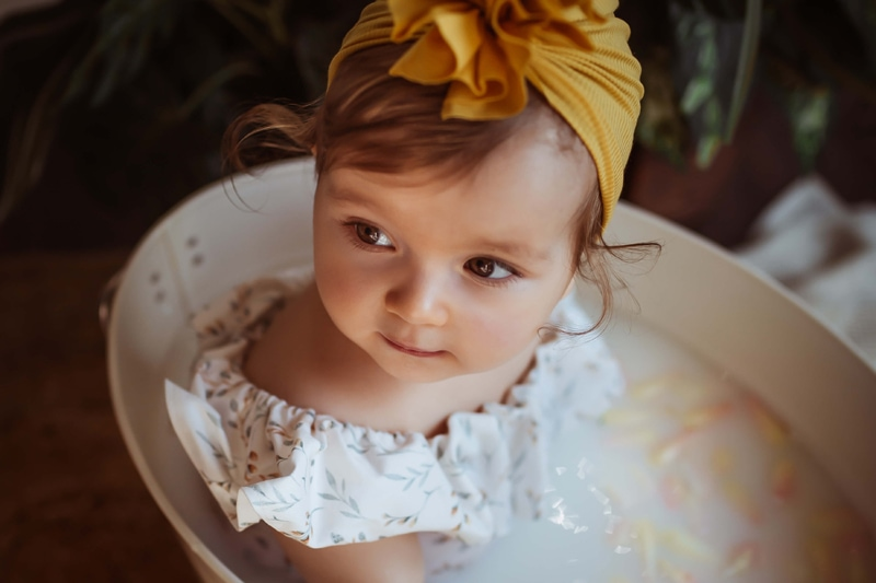 London Family Photographer, little baby girl sits in a large metal bucket in a flower and milk bath