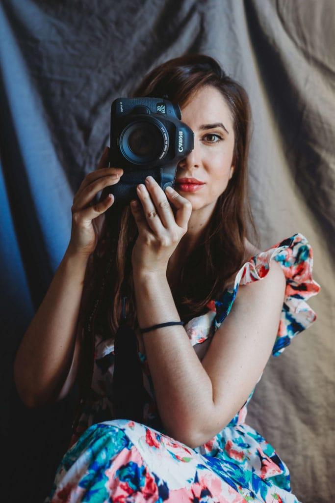 Headshot of Aida Llanos, holding camera up to her eye