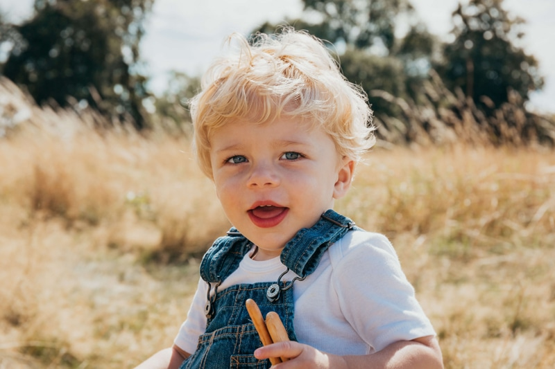 London Family Photographer, little boy sits in dry grassy field happy with his snacks