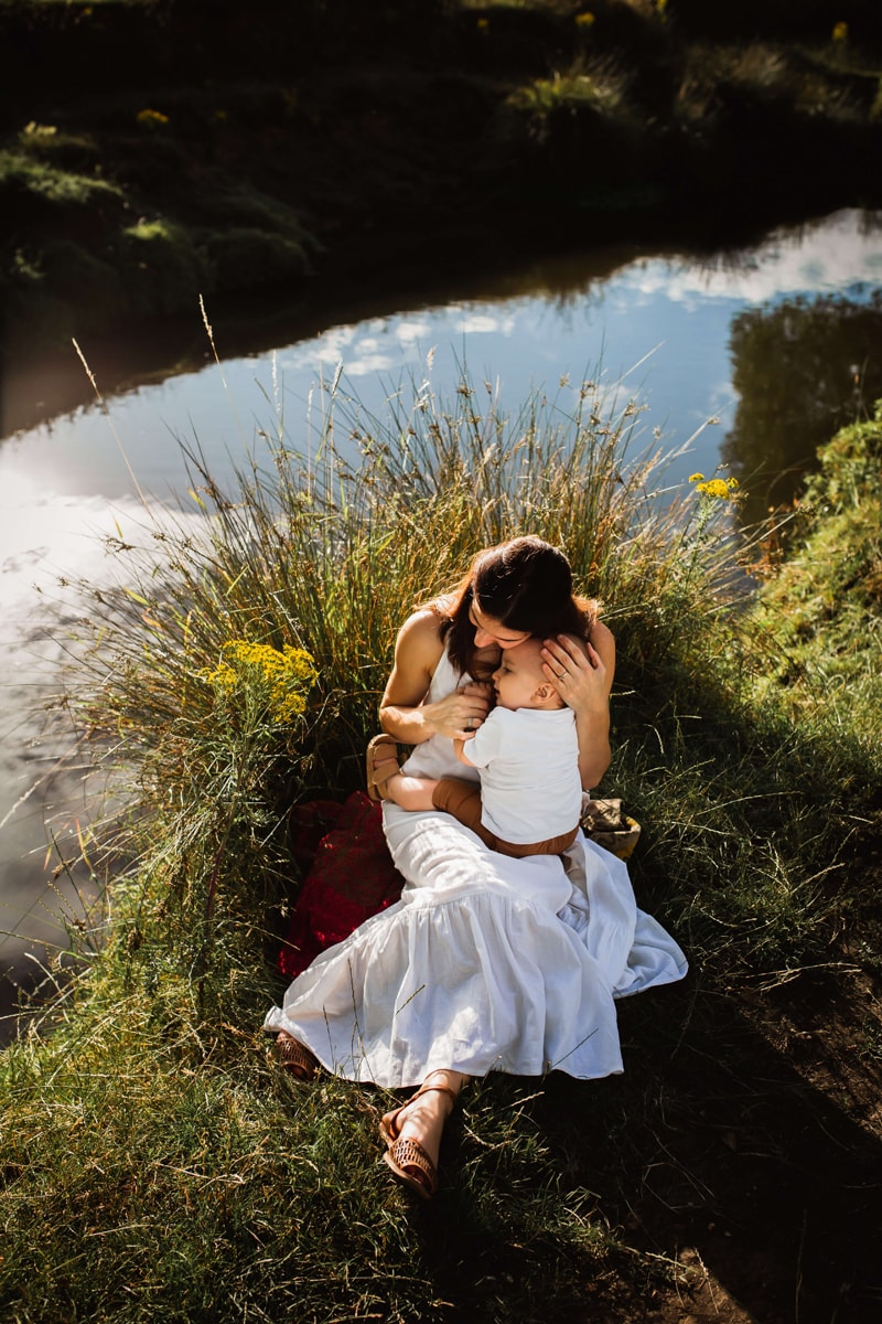 London Family Photographer, a young mother in a white dress holds onto her newborn baby sun near a stream