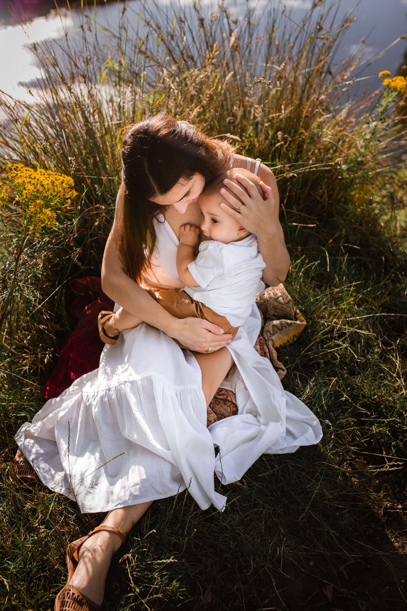 London Family Photographer, a woman holds onto her baby as they sit near a lakes flowers and reeds