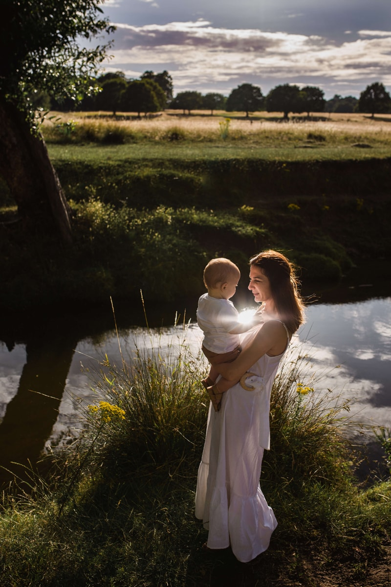 London Family Photographer, a woman holds her baby near a quiet stream, the clouds reflect in the water