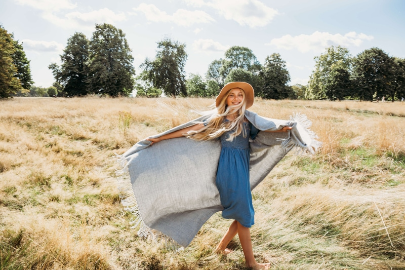 London Family Photographer, a young woman runs with her blanket floating in a dry grassy field