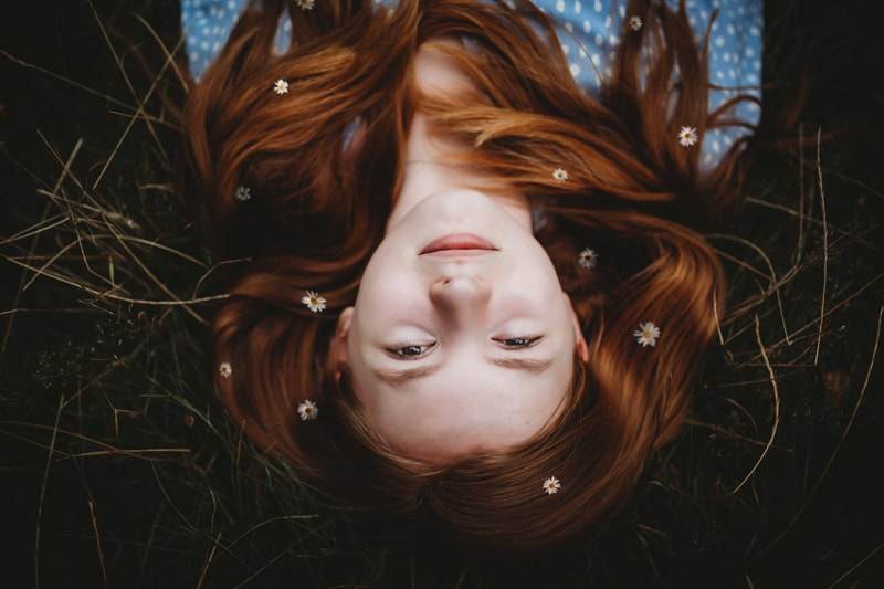 London Family Photographer, Red head girl lays in the grass with tiny white flowers in her hair