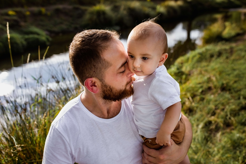 London Family Photographer, a young father cuddles into his baby son outdoors