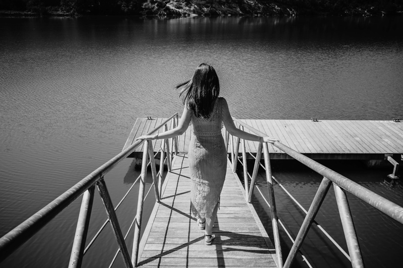 London Family Photographer, a woman holds onto a small boat docs rails as she walks toward the water