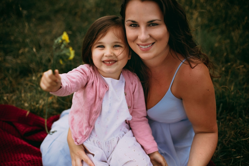 London Family Photographer, a mom smiles holding onto her young daughter, the daughter holds freshly-picked flowers