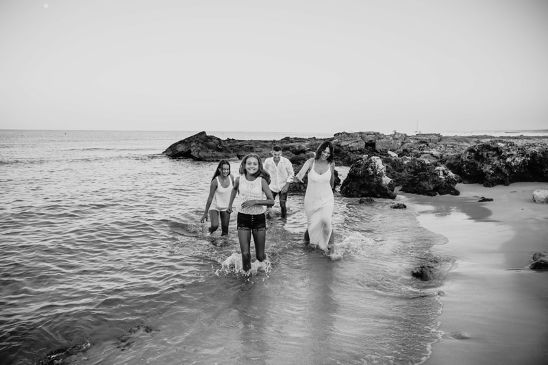 London Family Photographer, a family with two young daughters all splash through the beach waves