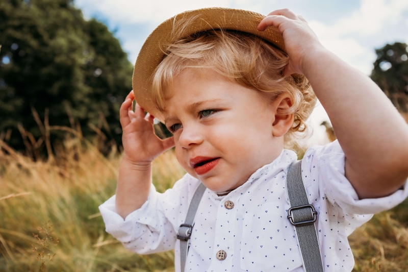 London Family Photographer, little toddler boy holds onto his at on a windy day outdoors