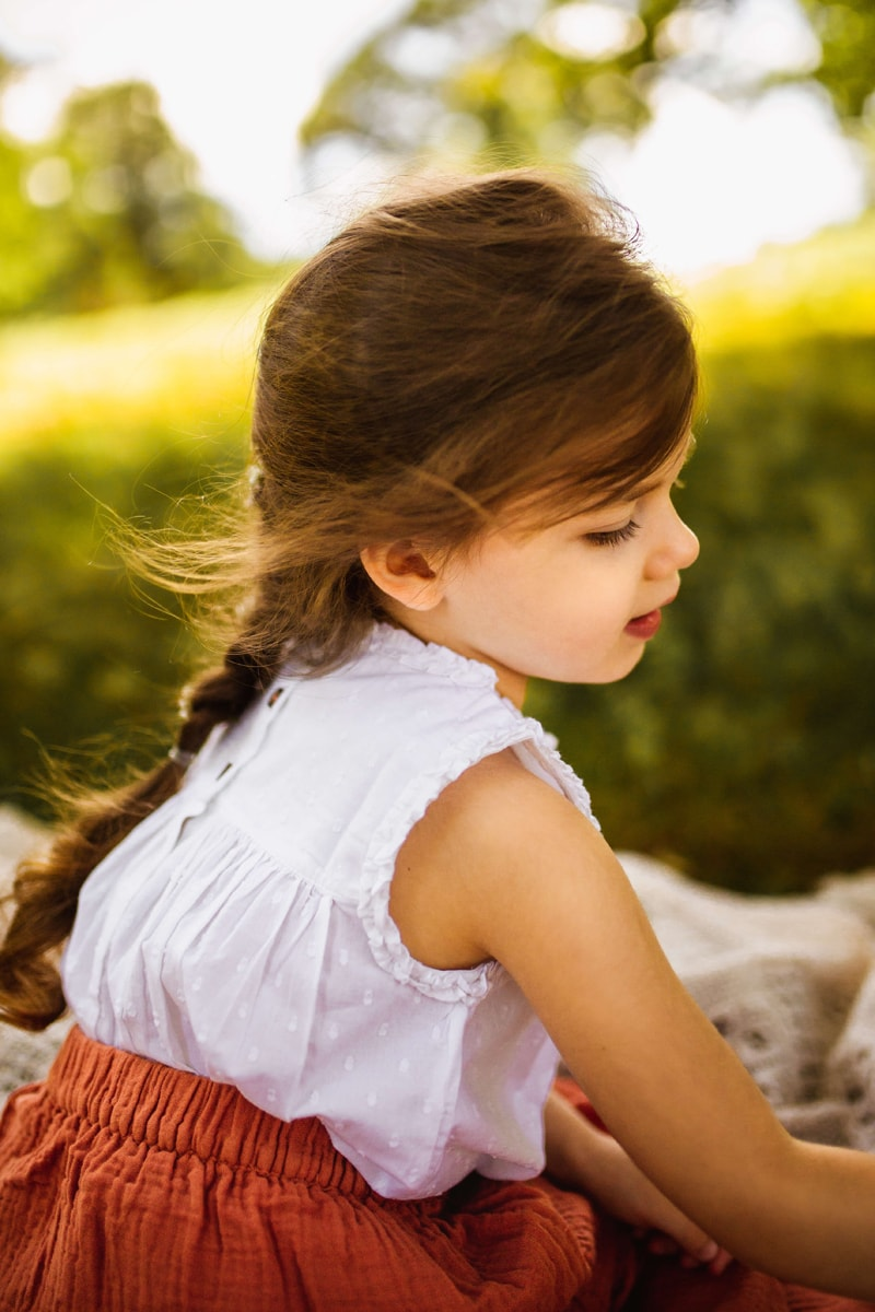 London Family Photographer, little toddler girl is happy on a blanket outdoors