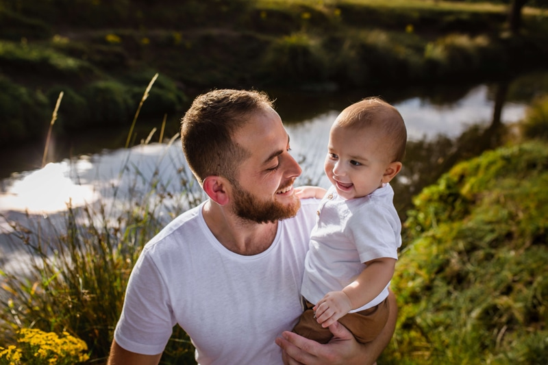 London Family Photographer, a young father looks at his baby son smiling, they are outside near a quiet stream